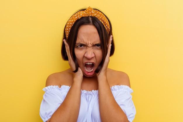 너무 시끄러운 소리를 듣지 않으려 고 손으로 귀를 덮고 노란색 배경에 고립 된 젊은 혼합 된 인종 여자.
