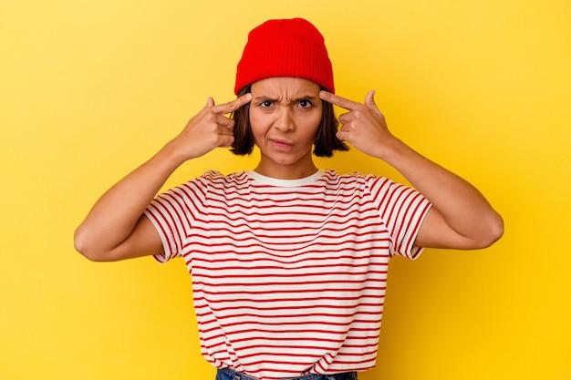 Молодая женщина смешанной расы, изолированная на желтом фоне, сосредоточилась на задаче, держа указательные пальцы, указывая головой.