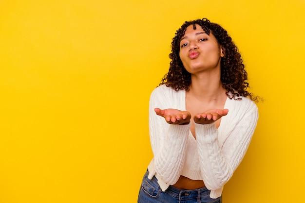 黄色の背景に分離された若い混血の女性は、唇を折り、手のひらを持って空気のキスを送信します。