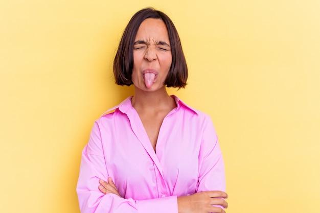 Молодая женщина смешанной расы, изолированные на желтом фоне, смешно и дружелюбно высунув язык.