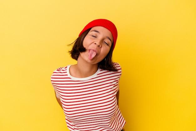 舌を突き出して面白いとフレンドリーな黄色の背景に分離された若い混血女性。