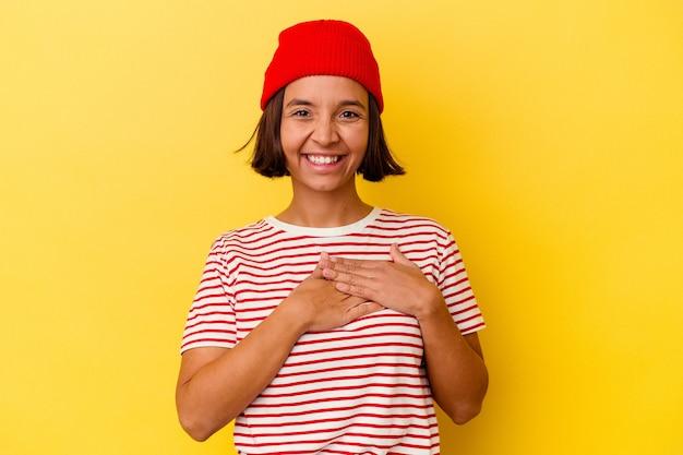 黄色の背景に分離された若い混血の女性は、手のひらを胸に押し付けてフレンドリーな表情をしています。愛の概念。