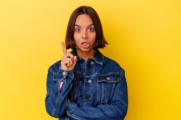 アイデア、インスピレーションの概念を持つ黄色の背景に分離された若い混血女性。