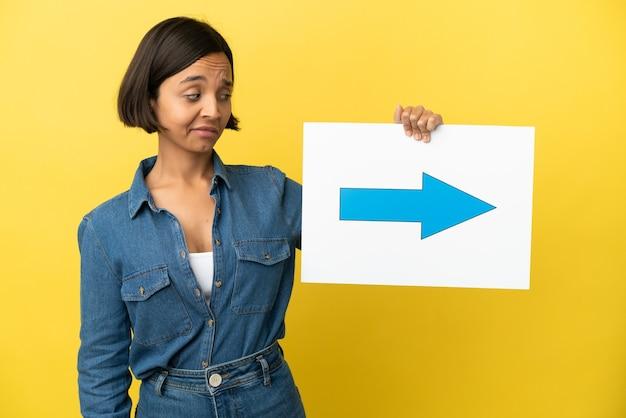 矢印記号のプラカードを保持している黄色の背景に分離された若い混血の女性