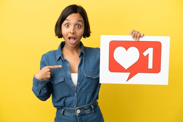 Молодая женщина смешанной расы изолирована на желтом фоне, держа плакат со значком `` нравится '' и указывая на него