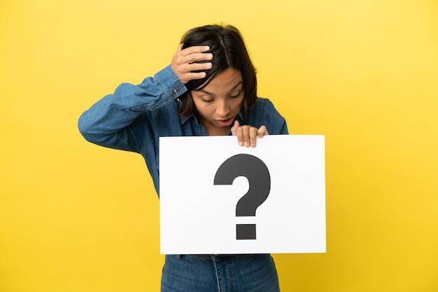 Молодая женщина смешанной расы изолирована на желтом фоне, держа плакат с символом вопросительного знака с удивленным выражением лица