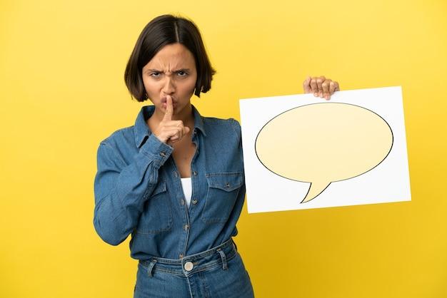Молодая женщина смешанной расы изолирована на желтом фоне, держа плакат со значком речевого пузыря, делая жест молчания