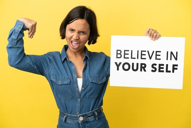 黄色の背景に分離された若い混血の女性は、テキストを信じてあなたの自己を信じて、強いジェスチャーをしているプラカードを保持しています