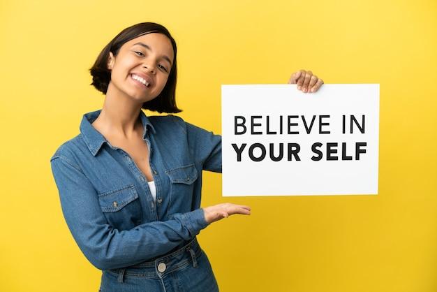 Молодая женщина смешанной расы изолирована на желтом фоне, держа плакат с текстом верю в себя и указывая на него