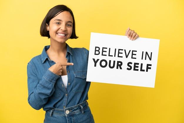 黄色の背景に分離された若い混血の女性は、テキストbelieve in yourselfとそれを指しているプラカードを保持しています。