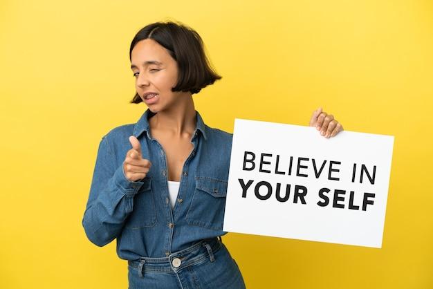 Молодая женщина смешанной расы изолирована на желтом фоне, держа плакат с текстом «верь в себя» и указывая на фронт