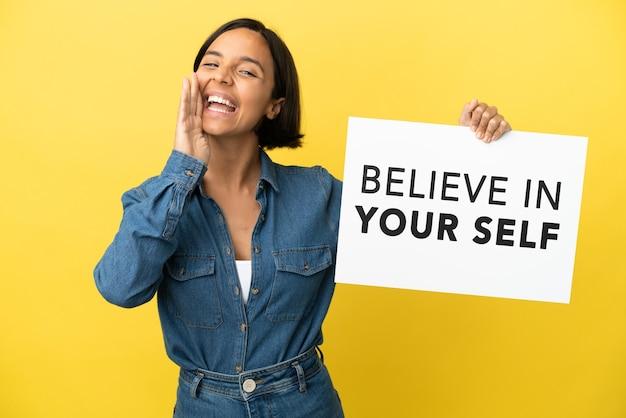 Молодая женщина смешанной расы, изолированная на желтом фоне, держит плакат с текстом «верь в себя» и кричит