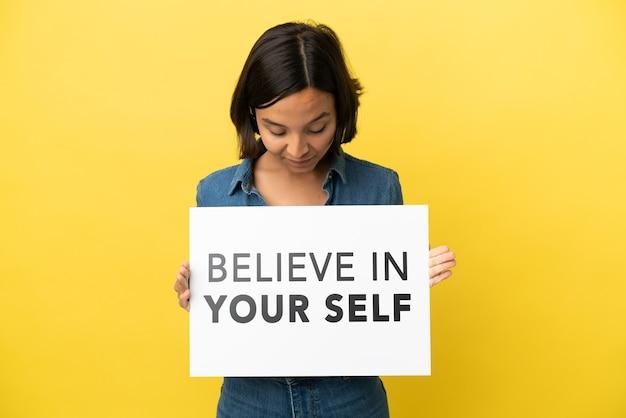 Молодая женщина смешанной расы изолирована на желтом фоне, держа плакат с текстом верю в себя