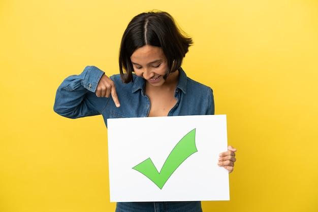 텍스트 녹색 확인 표시 아이콘으로 현수막을 들고 그것을 가리키는 노란색 배경에 고립 된 젊은 혼합 된 인종 여자