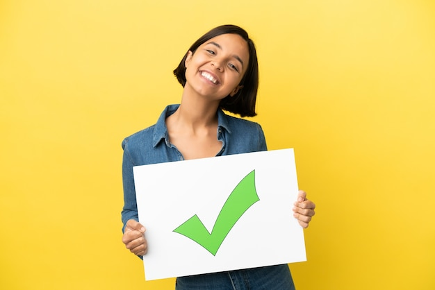행복 한 표정으로 텍스트 녹색 확인 표시 아이콘으로 현수막을 들고 노란색 배경에 고립 된 젊은 혼혈 여자