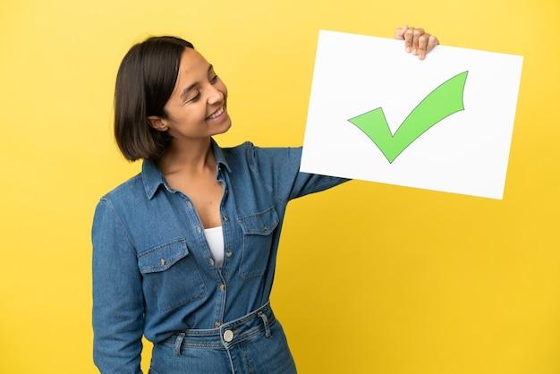 노란색 배경에 격리된 젊은 혼혈 여성 텍스트가 있는 플래카드를 들고 행복한 표정으로 녹색 확인 표시 아이콘