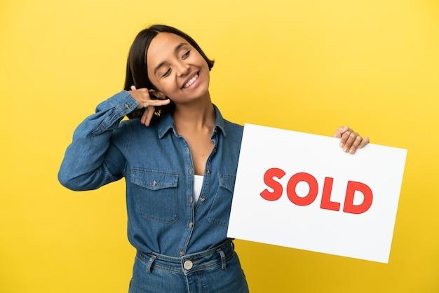 Молодая женщина смешанной расы изолирована на желтом фоне, держа плакат с текстом продано и делая приближающийся жест