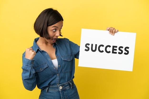 텍스트 성공과 플래 카드를 들고 승리를 축하하는 노란색 배경에 고립 된 젊은 혼합 된 인종 여자