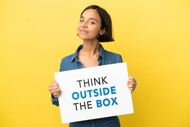텍스트와 플래 카드를 들고 노란색 배경에 고립 된 젊은 혼합 된 인종 여자는 상자 밖에 생각