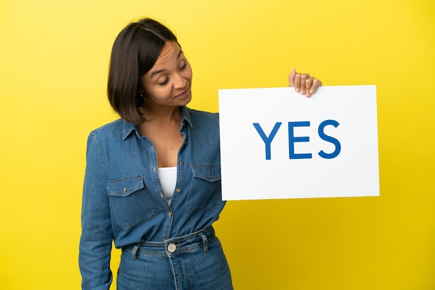 テキストyesのプラカードを保持している黄色の背景に分離された若い混血の女性