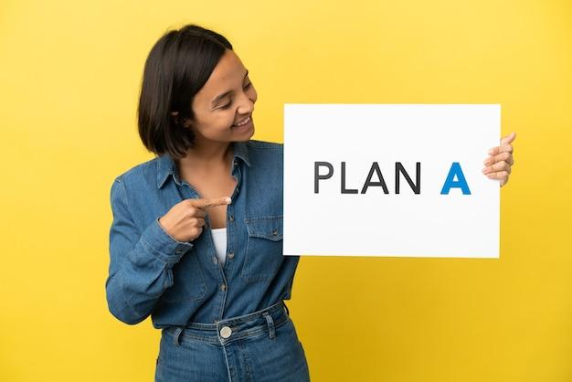 Молодая женщина смешанной расы изолирована на желтом фоне, держа плакат с сообщением план а и указывая на него