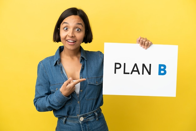 Молодая женщина смешанной расы изолирована на желтом фоне, держа плакат с сообщением план b с удивленным выражением лица