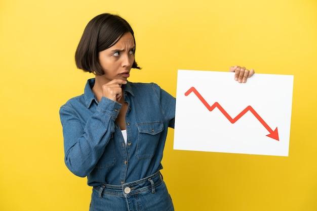 감소 통계 화살표 기호와 생각으로 기호를 들고 노란색 배경에 고립 된 젊은 혼합 된 인종 여자