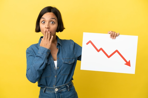 Молодая женщина смешанной расы изолирована на желтом фоне с табличкой с уменьшающимся символом стрелки статистики с удивленным выражением лица
