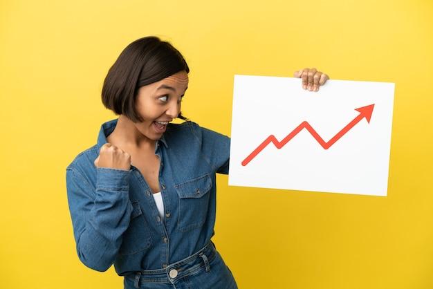 成長する統計矢印記号と勝利を祝う看板を保持している黄色の背景に分離された若い混血の女性