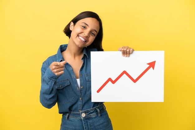 成長している統計矢印記号と正面を指している看板を保持している黄色の背景に分離された若い混血の女性