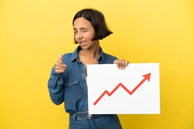 노란색 배경에 격리된 젊은 혼혈 여성은 성장하는 통계 화살표 기호가 있는 표지판을 들고 앞을 가리키고 있습니다.