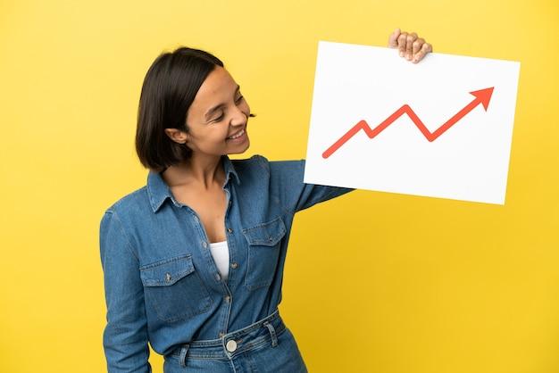黄色の背景に分離された若い混血の女性は、幸せな表現と成長統計矢印記号のサインを保持