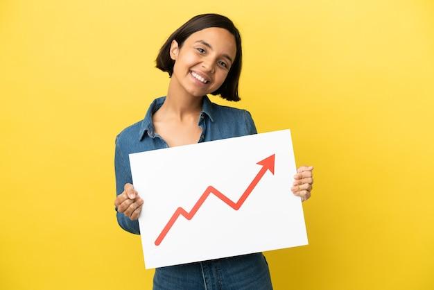 幸せな表情で成長している統計矢印記号の付いた看板を持っている黄色の背景に分離された若い混血女性