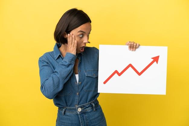 Молодая женщина смешанной расы изолирована на желтом фоне с табличкой с растущим символом стрелки статистики с удивленным выражением лица