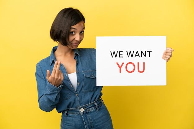 Молодая женщина смешанной расы, изолированная на желтом фоне, держит доску we want you и делает приближающийся жест
