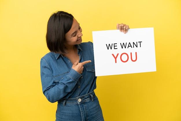 Молодая женщина смешанной расы изолирована на желтом фоне, держа доску we want you и указывая на нее