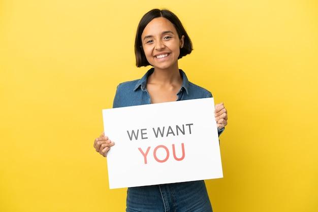 Молодая женщина смешанной расы изолирована на желтом фоне, держа доску we want you с счастливым выражением лица