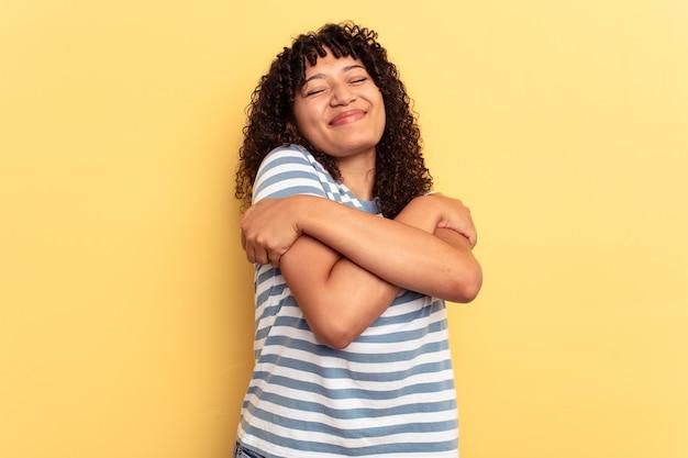 黄色の背景の抱擁に分離された若い混血の女性は、のんびりと幸せに笑っています。