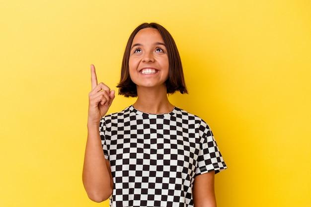 노란색 배경에 고립 된 젊은 혼혈 여자는 빈 공간을 보여주는 두 앞 손가락으로 나타냅니다.