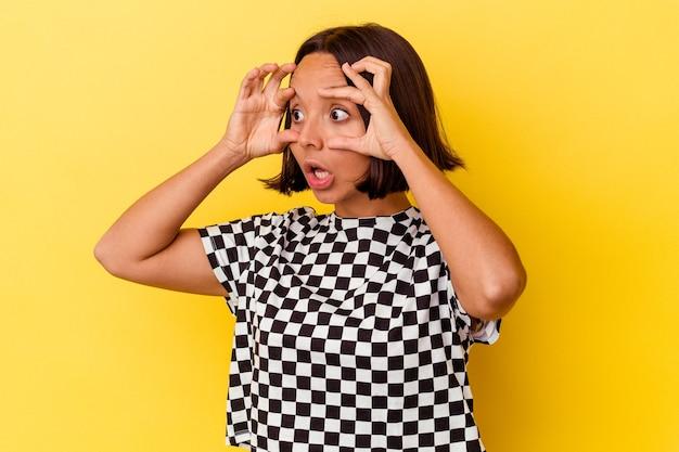 성공 기회를 찾기 위해 눈을 유지 노란색 배경에 고립 된 젊은 혼합 된 인종 여자.
