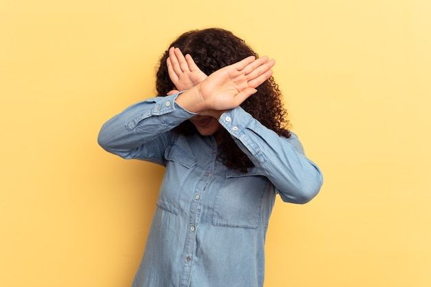Молодая женщина смешанной расы изолирована на желтом фоне, держа скрещенными руками, концепцию отрицания.
