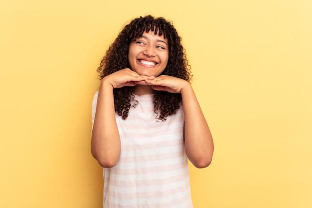Молодая женщина смешанной расы, изолированные на желтом фоне, держит руки под подбородком, счастливо смотрит в сторону.