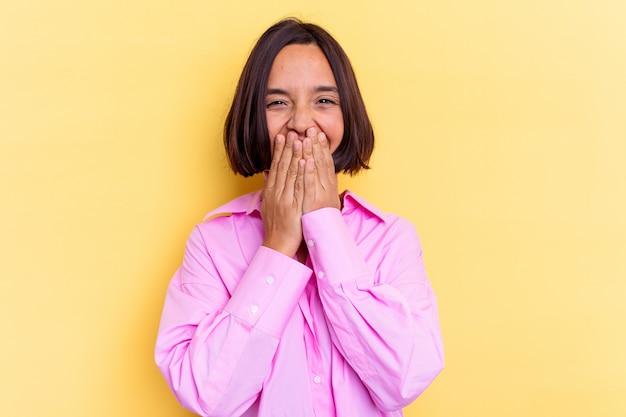 Молодая женщина смешанной расы, изолированные на желтом фоне, смеясь над чем-то, прикрывая рот руками.