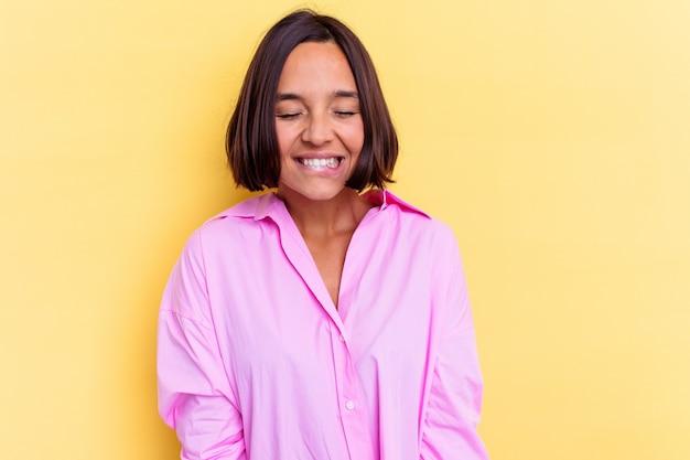 黄色の背景に分離された若い混血の女性は笑って目を閉じ、リラックスして幸せを感じます。