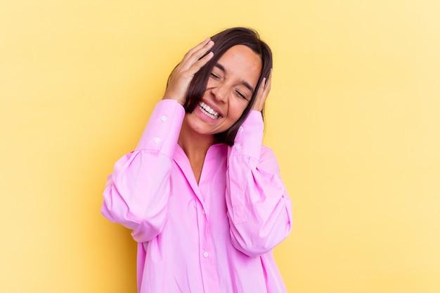 Молодая женщина смешанной расы, изолированные на желтом фоне, радостно смеется, держа руки на голове. концепция счастья.