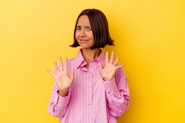 Молодая женщина смешанной расы изолирована на желтом фоне, отвергая кого-то, показывая жест отвращения. Premium Фотографии