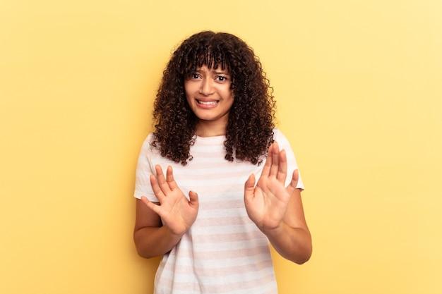 Молодая женщина смешанной расы изолирована на желтом фоне, отвергая кого-то, показывая жест отвращения.