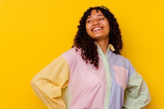 Молодая женщина смешанной расы изолирована на желтом фоне расслабленным и счастливым смехом, вытянув шею, показывая зубы.
