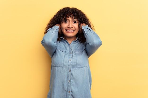 Молодая женщина смешанной расы, изолированные на желтом фоне, кричать от ярости.