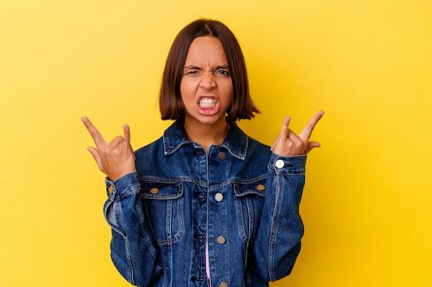 Молодая женщина смешанной расы изолирована на желтом фоне, показывая жест рогов как понятие революции.